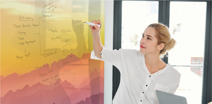 Stock image of a girl writing on a writable surface